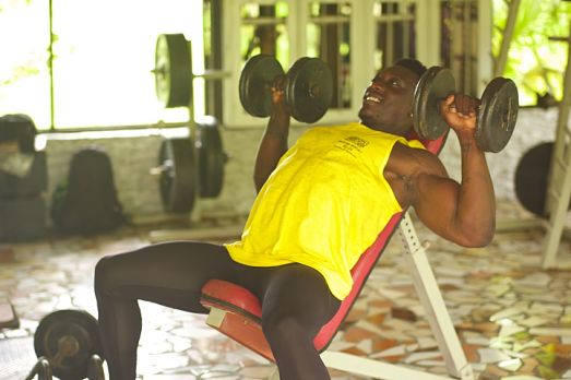 athletic man working out with weights in the Weights Room at Belize Boutique Resort & Spa