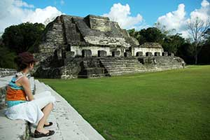 lady sitting on Maya Temple at Altun Ha May ruins site